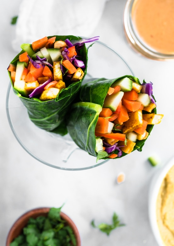 Rainbow wraps filled with colorful veggies wrapped in a collard green. Served next to a side of creamy peanut sauce.