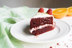 A piece of layered red velvet cake with orange halves in the background.