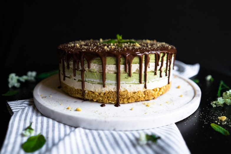 Layered matcha cheesecake with mint chocolate ganache dripping over the edges.