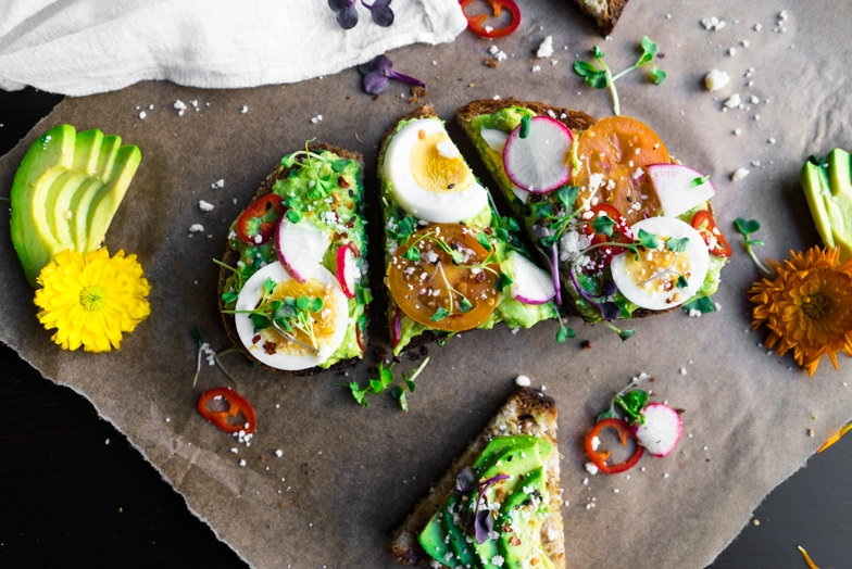 A slice of spring avocado toast with hard boiled eggs, radishes, and Fresno chilis cut into pieces.