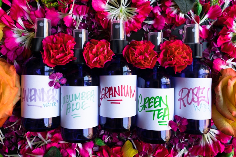 5 DIY facial mists for glowing skin lying on a bed of flower petals.
