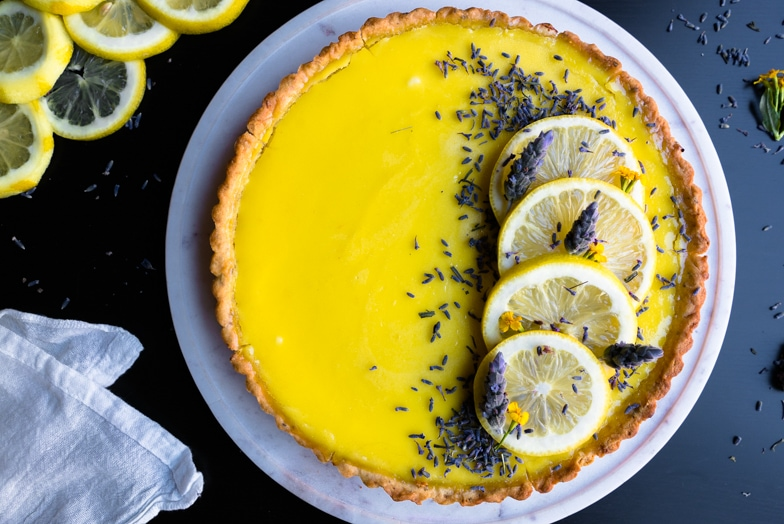 Bright yellow lavender scented lemon tart decorated with lemon slices and lavender flowers.
