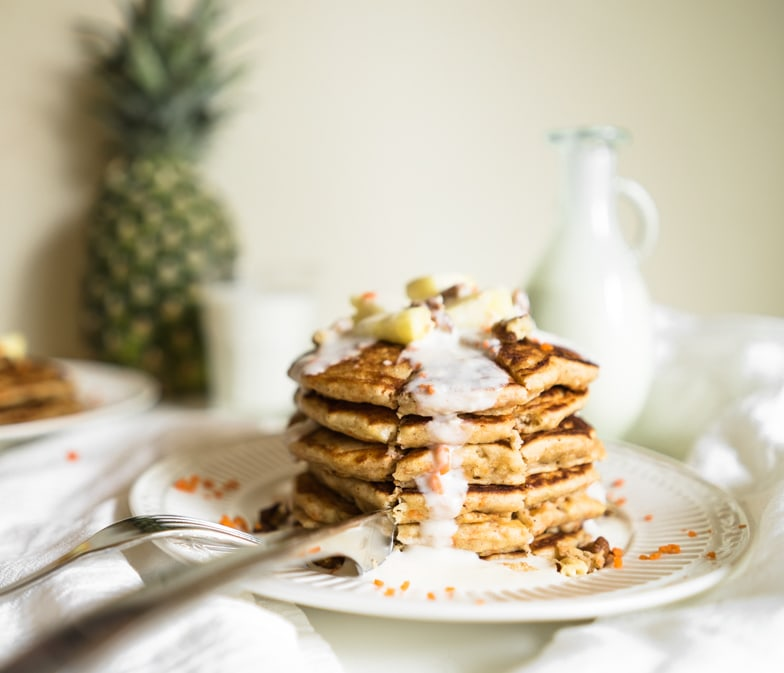 Stack of carrot cake pancakes with pineapple cream cheese drizzle being cut into with a butterknife.