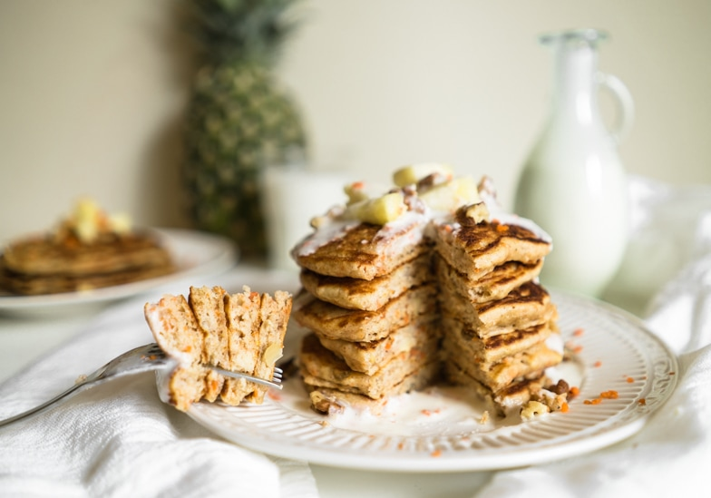 Stack of carrot cake pancakes with pineapple cream cheese drizzle being eaten with a fork.