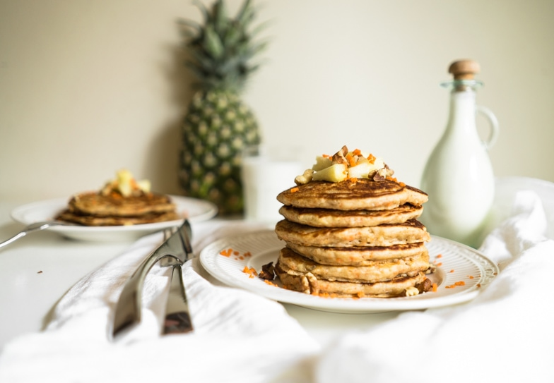 Stack of carrot cake pancakes with pineapple cream cheese drizzle next to it.