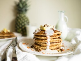 Stack of carrot cake pancakes with pineapple cream cheese drizzle.