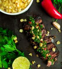 Steak chimichurri with grilled corn next to fresh ingredients.