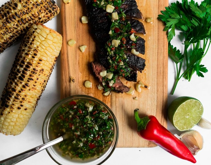 Sliced skirt steak on a cutting board next to chimichurri sauce and fresh ingredients.