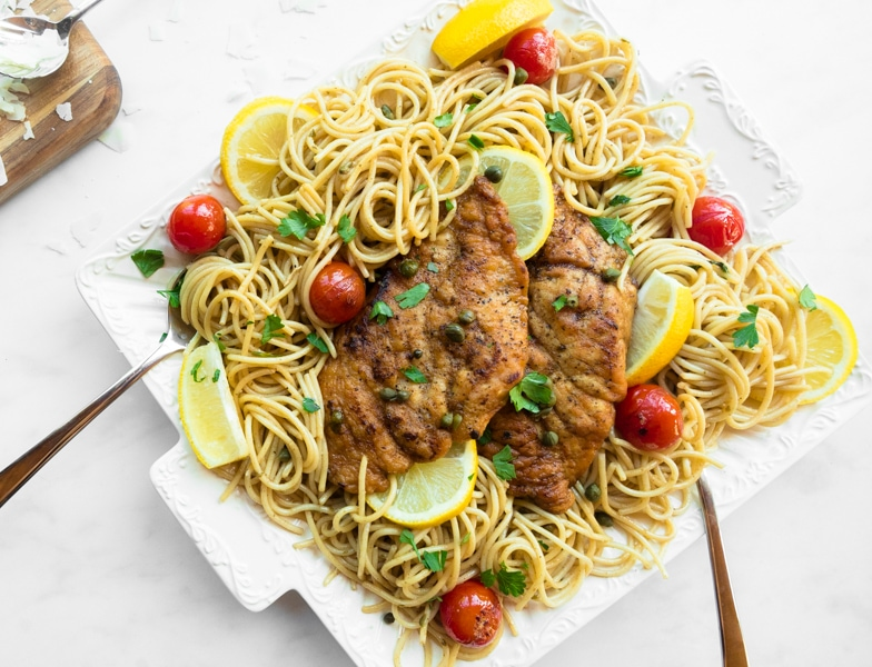 Platter of spaghetti topped with lemony chicken piccata and burst cherry tomatoes.