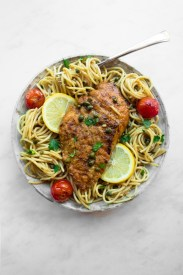 Bowl of spaghetti topped with lemony chicken piccata and burst cherry tomatoes.