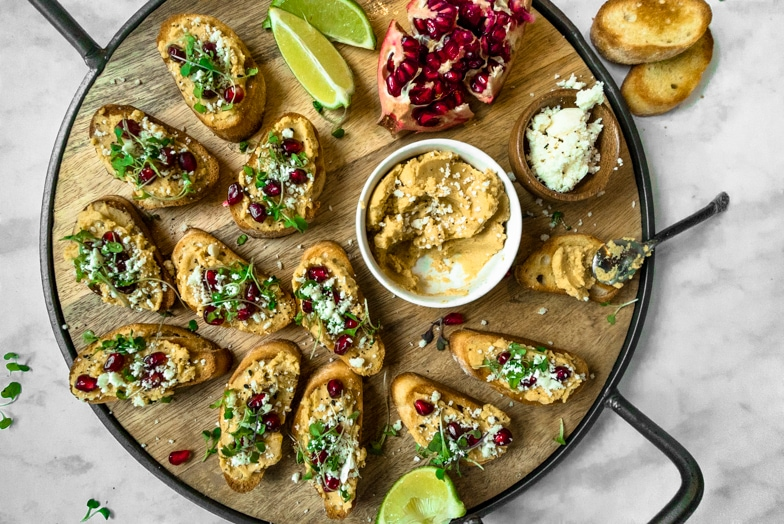 Platter of crostini with butternut squash hummus, pomegranate arils, micro greens, and Cotija cheese.
