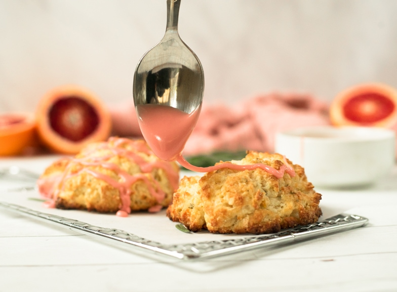 Rosemary Irish soda scone being drizzled with a blood orange glaze.