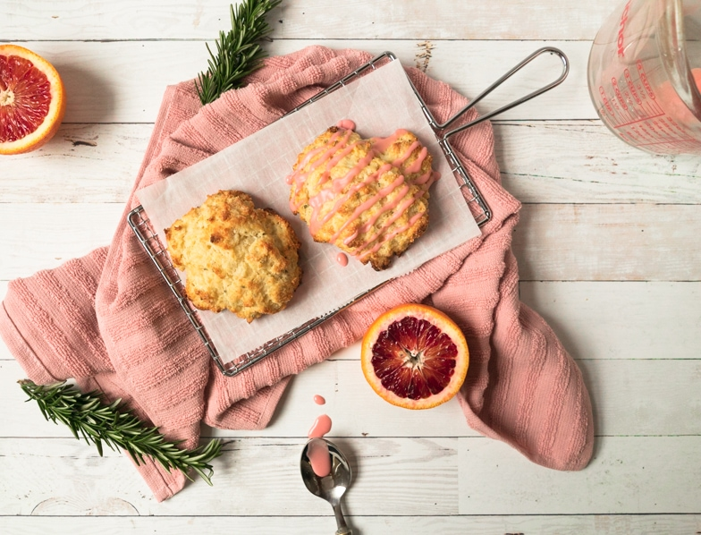 Two rosemary Irish soda scones next to a spoon with a trail of glaze and fresh rosemary sprigs and blood oranges surrounding them.