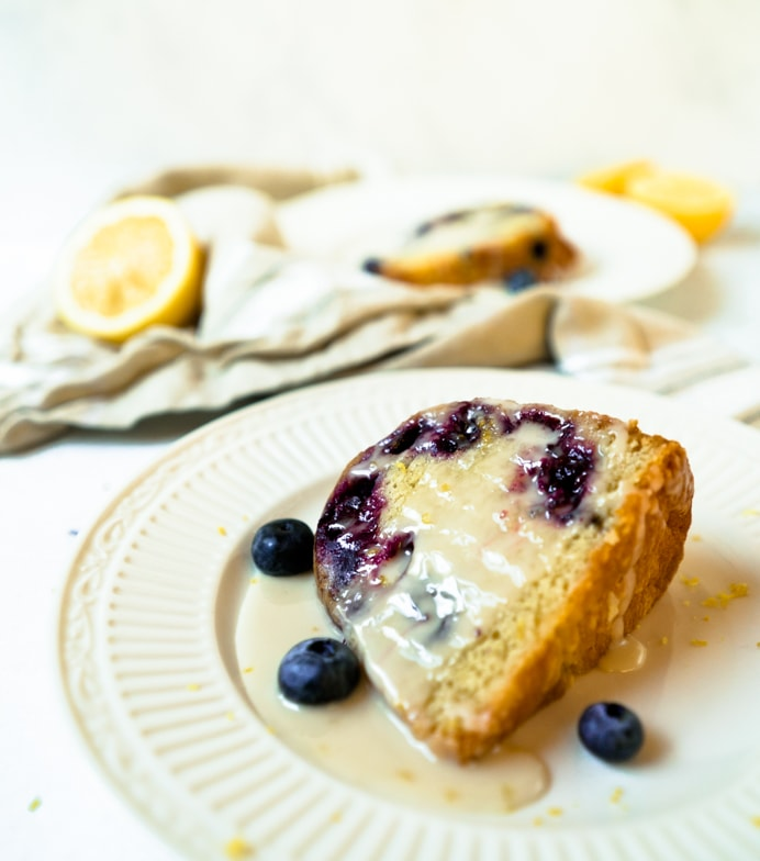 Close up of a blueberry muffin cake slice dripping with lemon glaze and garnished with fresh blueberries and lemon zest.
