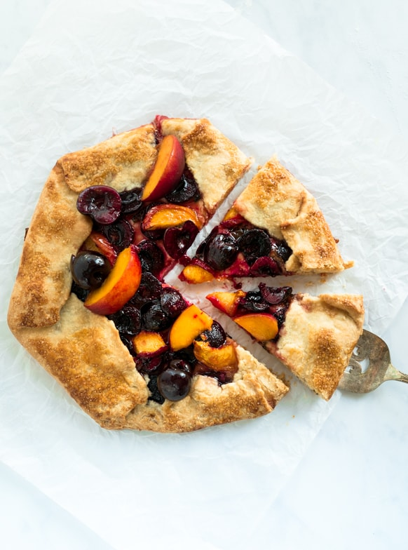 Cherry peach goat cheese galette on white parchment paper with two slices being served.