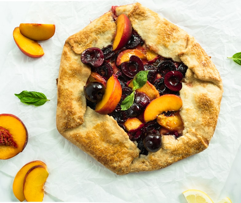 Cherry peach galette with fresh basil surrounded by juicy peaches.