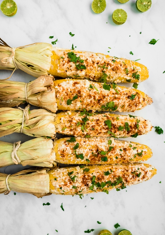 Five ears of Mexican street corn with their husks tied back lined up in a row. Garnished with cilantro and limes.