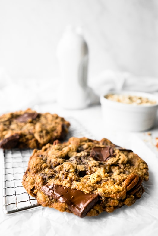 Close up of giant pumpkin spice oatmeal cookie with melty chocolate and pecans.