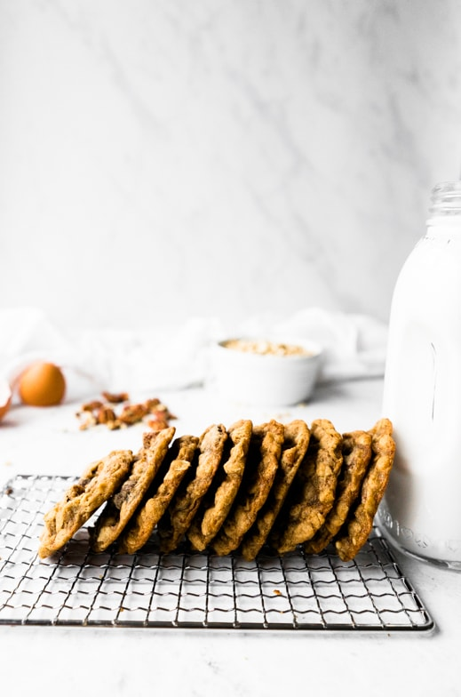 Smaller version of pumpkin spice oatmeal cookies all lined up leaning on a tall glass of milk with fresh ingredients in the background.