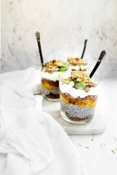 tropical fruit parfaits in a glass, layered with kiwi, mango, coconut chia pudding, and homemade granola.