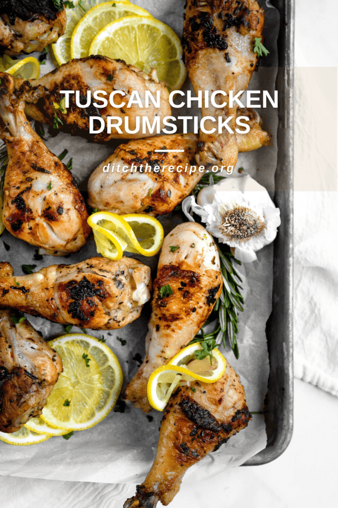 """Pan layered with Tuscan-style chicken drumsticks with text over top reading """"TUSCAN STYLE CHICKEN DRUMSTICKS — ditchtherecipe.org"""""""