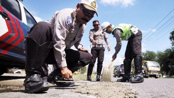 Kanit Patroli Satlantas Polres Lhokseumawe Ipda Rusdi AR menampal lubang di Jalan Medan-Banda Aceh, tepatnya di Blang Naleung Mameh, Kecamatan Muara Satu, Lhokseumawe, Jumat (15/7) | Serambinews.com