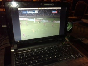 Football match Armenia - Macedonia on a laptop screen next to a projector