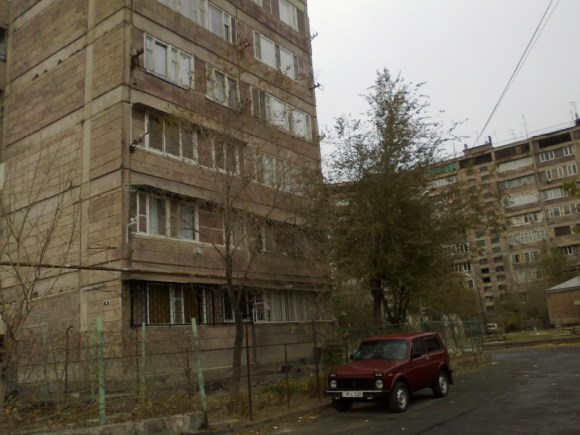 Photo of an appartment building and a Niva parked outside