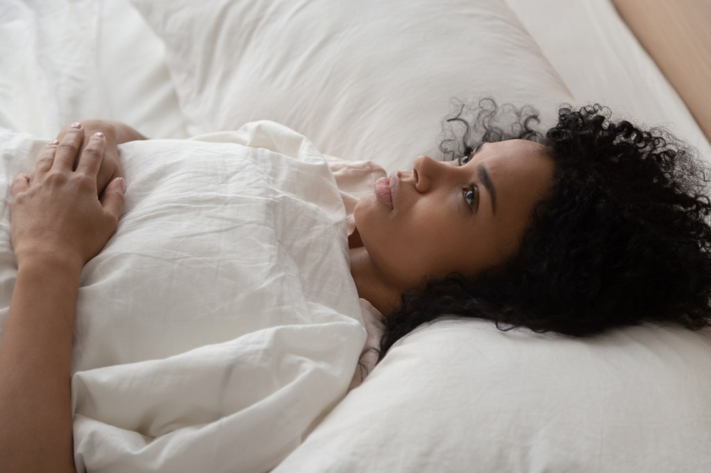 young Black woman laying in bed thinking about sleeping with a menstrual cup