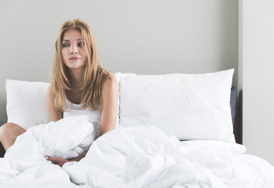 pensive young woman sitting in bed