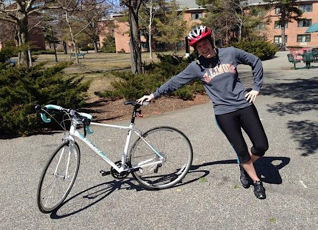 Bike & Build volunteer leaning on bicycle