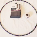 Picture with a white background, a purple hula hoop, a set of gray curtains and a roll of twine