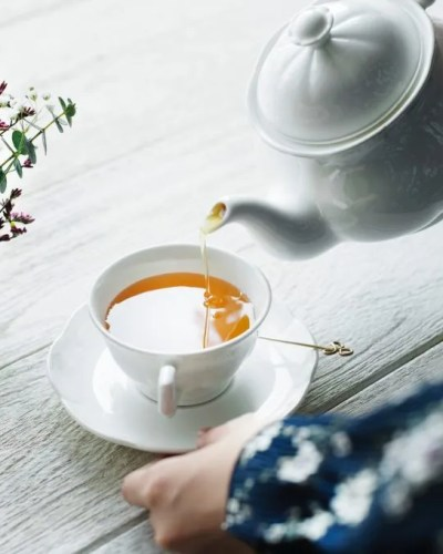 Tea being poured from a white ceramic teapot into a cup