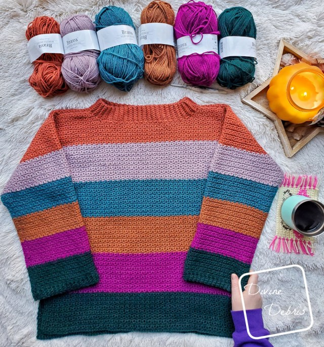 [image description] The Amelia Pullover crochet pattern striped sweater laying on a white blanket with 6 skeins of yarn and a hand holding the bottom right corner