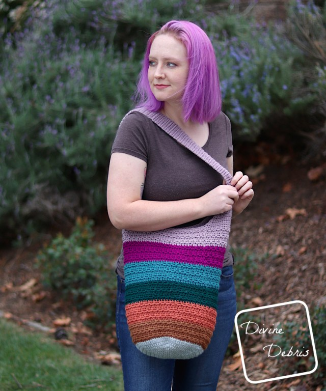 [image description] White woman with purple hair looks to the left while holding the strap of the striped Alix Bag, pulling it across her body.
