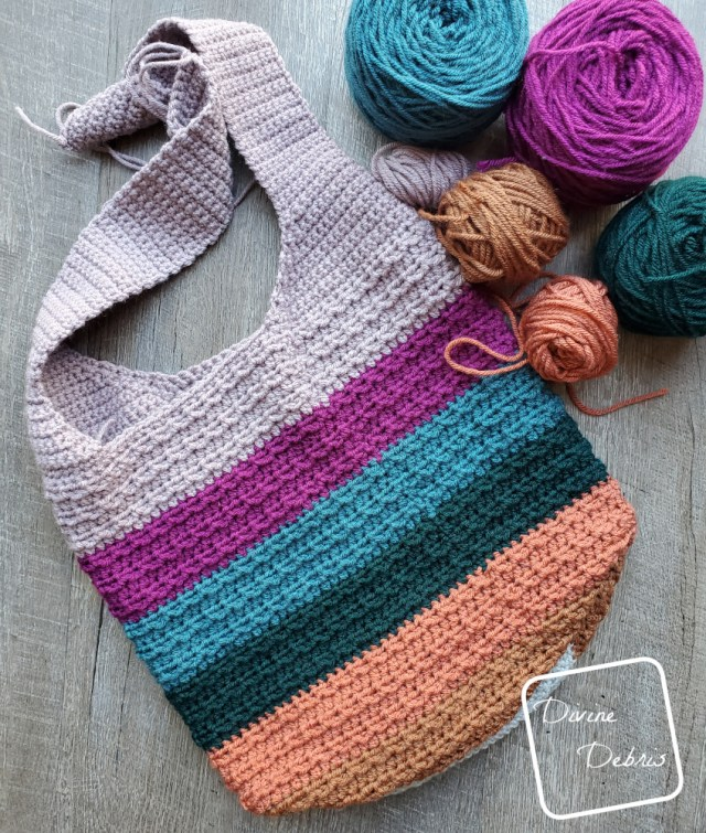 [Image description] Striped Alix Bag lays flat on the group, at an angle, with caked up yarn on the top right of the photo.