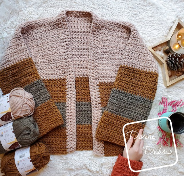 [image description] the Mia Cardigan lays flat on a white background with skeins of yarn to the left and a hand holding the right sleeve.