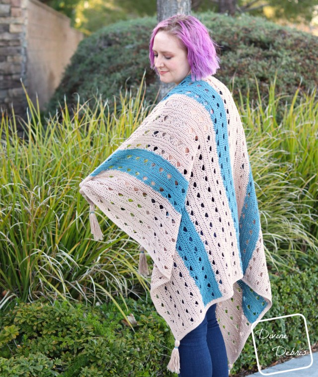 [Image description] A white woman purple hair looks to her left draped in the tan and blue striped Louise Blanket crochet pattern in front of green bushes.