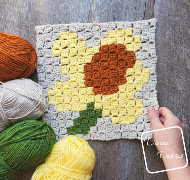 [Image description] C2C Daffodil Afghan Square laying in the center of the frame on a wood-grain background. One white hand holding the bottom right corner and 4 skeins of yarn (orange, beige, green, and yellow) on the bottom left corner.