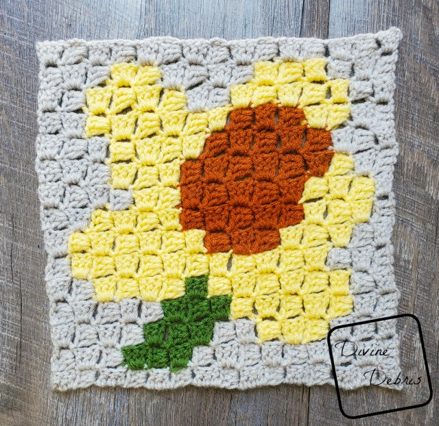 [Image description] C2C Daffodil Afghan Square laying in the center of the frame on a wood-grain background.