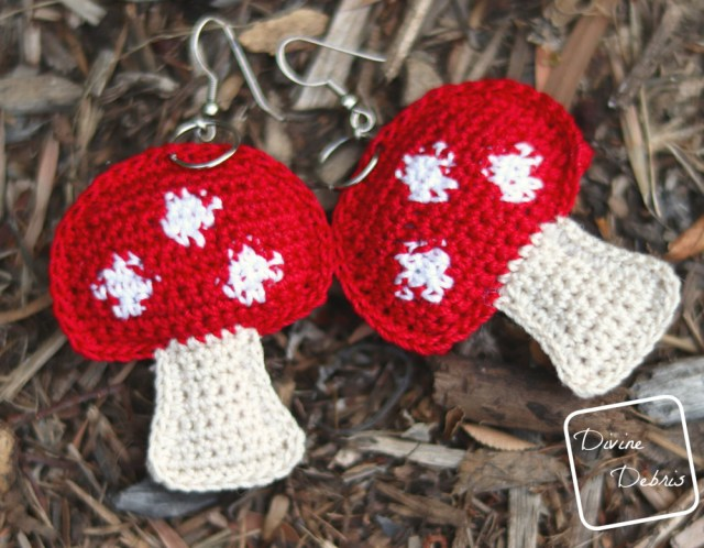 [Image description] A pair of red topped stuffed mushroom crochet earrings laying in on a bed of wood chips