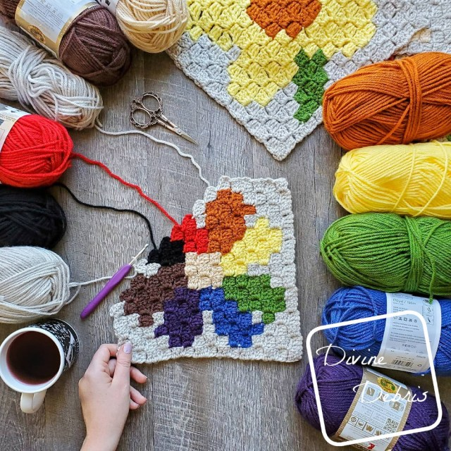 [Image description] the unfinished C2C Daisy Afghan Square lays on a wood background with a rainbow of yarn skeins along the right side of the frame, and skeins of tan, red, and black on the top. A white woman's had holds the bottom left corner of the square.
