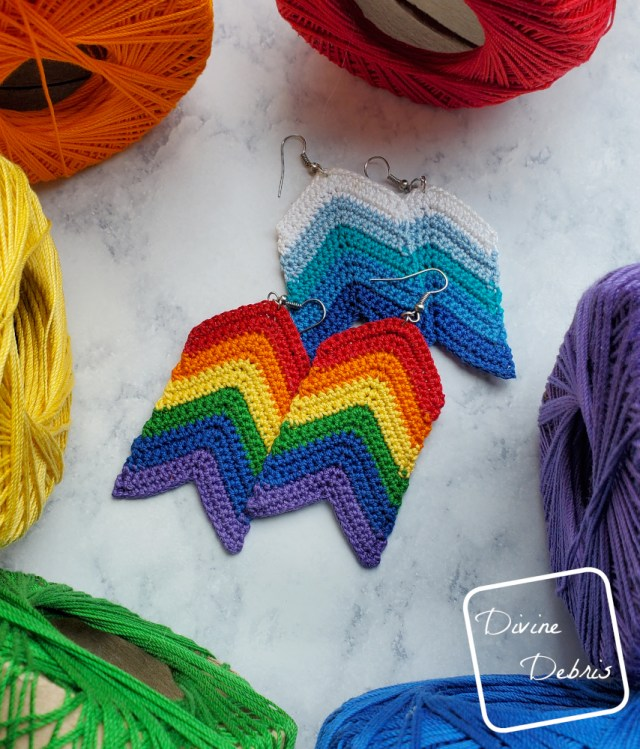 [Image description] Rainbow Arrow Earrings lay on top of a blue version of the Arrow Earrings, surrounded by rainbow skeins of thread on a stone looking surface
