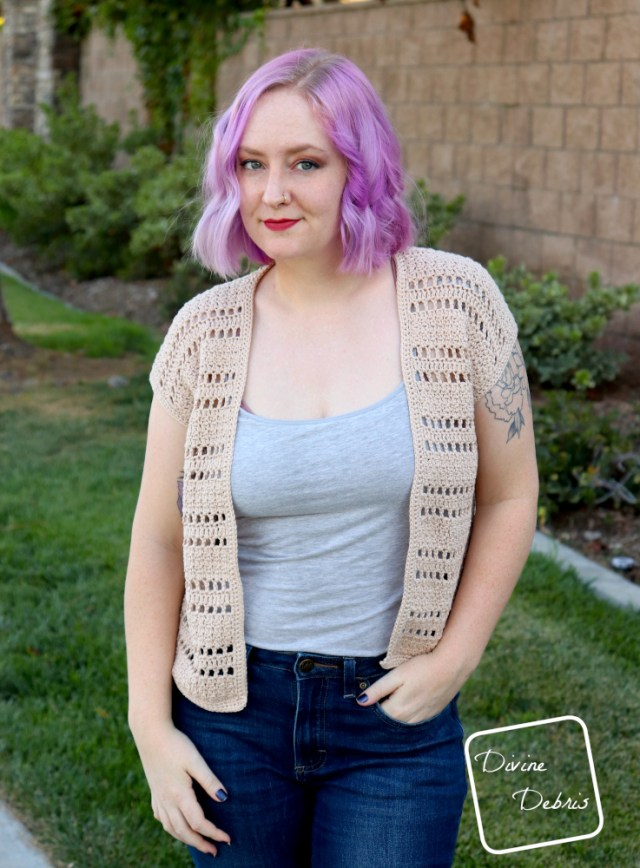[image description] a white woman with purple hair stands facing the viewer in front of a stone wall and green grass in the tan colored Kieran Cardigan crochet pattern.