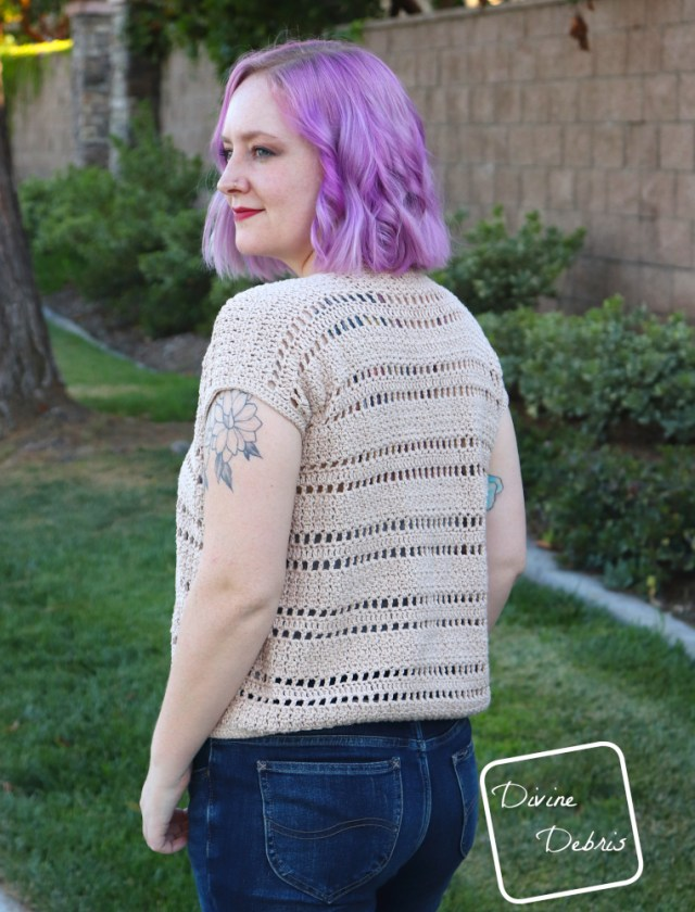 [image description] a white woman with purple hair stands with her back to the viewer looking to the left viewer in front of a stone wall and green grass in the tan colored Kieran Cardigan crochet pattern.