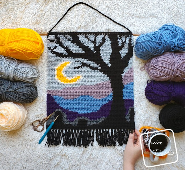 [Image description] The Cool Tree Wall-Hanging lays flat on a white background, framed by skeins of  yarn on the left and right. A white woman's had holds the bottom right corner of the wall-hanging with a cup of coffee to the right of her hand.
