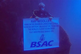 Ray Woolley holding a BSAC banner during his record dive on the wreck of the Zenobia. Screenshot © Granada Reports (BSAC | Vimeo | Fair Use)