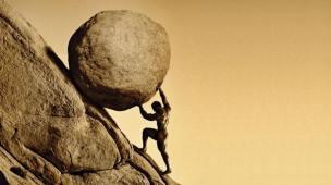 Homem levando pedra montanha acima