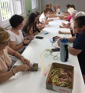 Participants de diferents edats aprenen a fer polseres d'aquesta entitat al casal cívic de Montcada i Reixac.