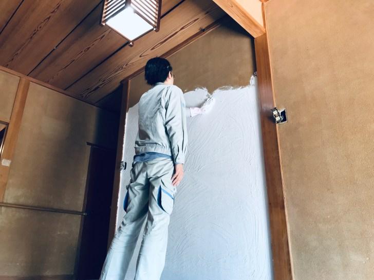 ゴム手袋を付けた左手で漆喰を塗る様子